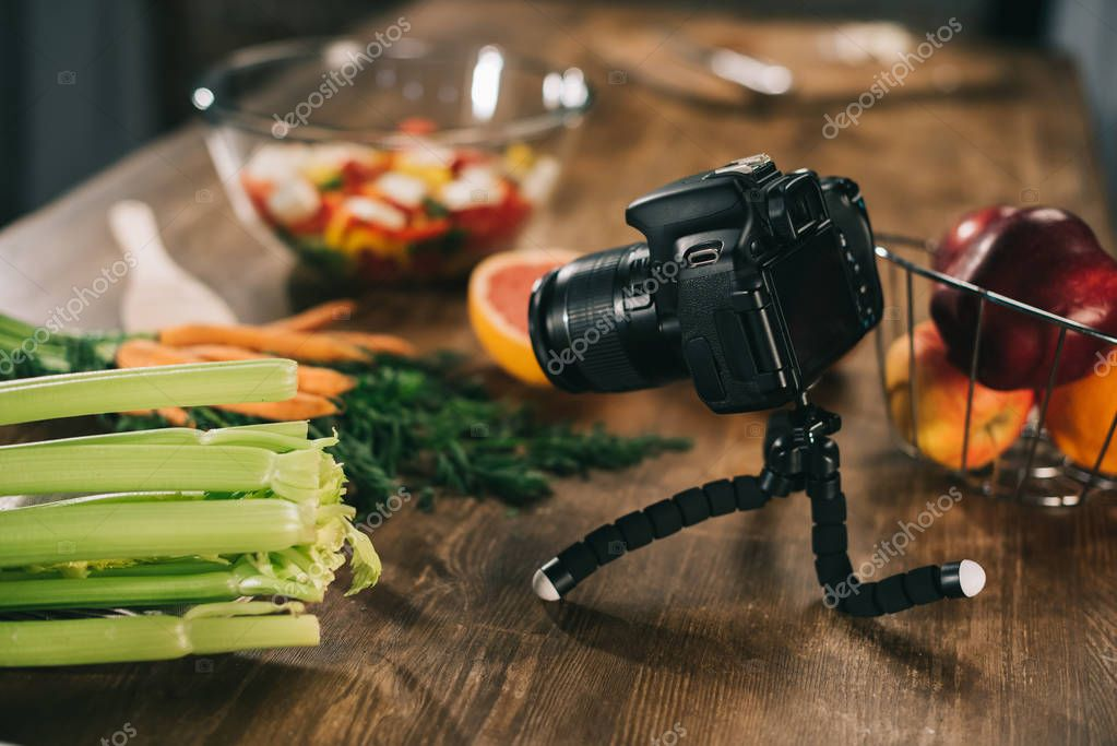 digital camera and vegetables on wooden tabletop