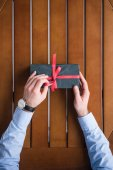 cropped image of man tying red ribbon on present box