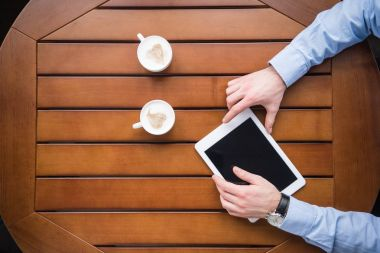 cropped image of man holding tablet and sitting at table with two cups of coffee