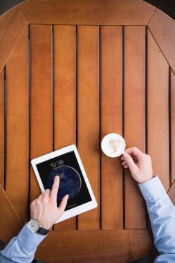 cropped image of man sitting with coffee and ipad tablet