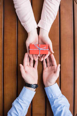 cropped image of girlfriend gifting present box to boyfriend