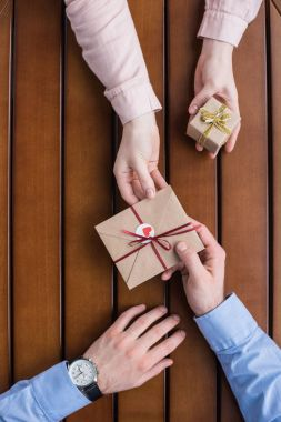 cropped image of girlfriend gifting postcard in envelope and present box to boyfriend