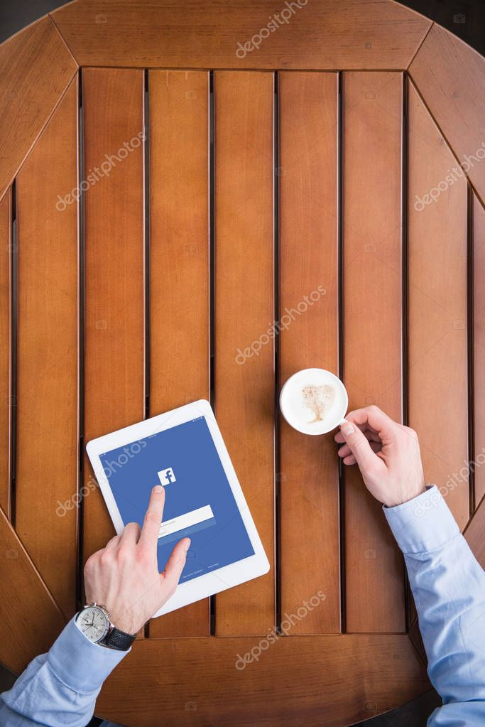 cropped image of man sitting with coffee and loaded facebook page on tablet