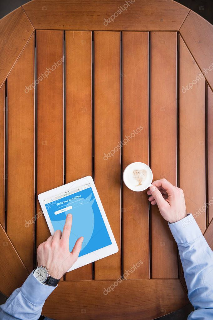 cropped image of man sitting with coffee and loaded twitter page on tablet