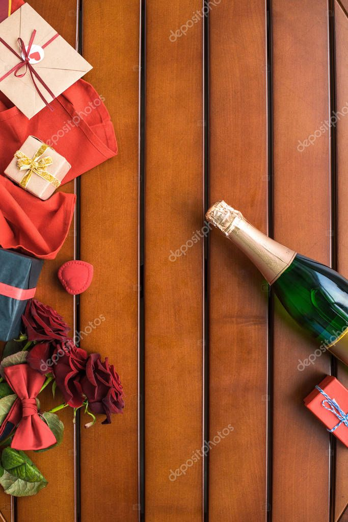 top view of champagne bottle with presents on wooden table