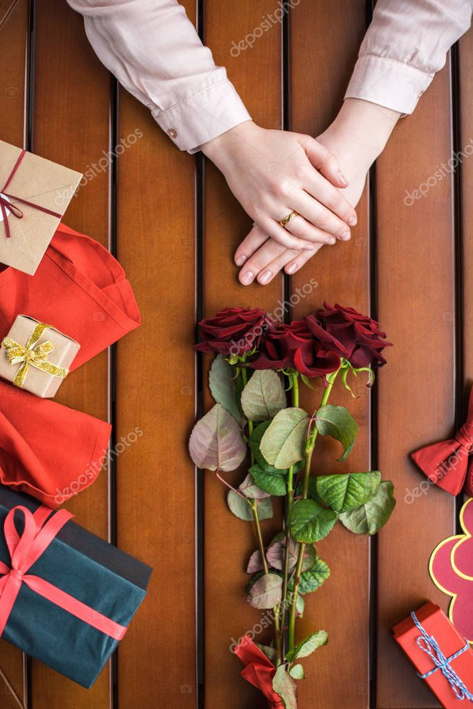 cropped image of woman sitting with bouquet of roses and presents on table