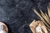 Fotografie Draufsicht von rohen Eiern, Mehl und Weizen auf dunklen Marmor Oberfläche