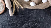 Photo flat lay with wheat, raw eggs on sack cloth and wooden rolling pin on dark marble surface