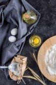 Fotografie plochý ležela s různými přísadami pro pečení chleba a příbory na tmavý mramor povrch