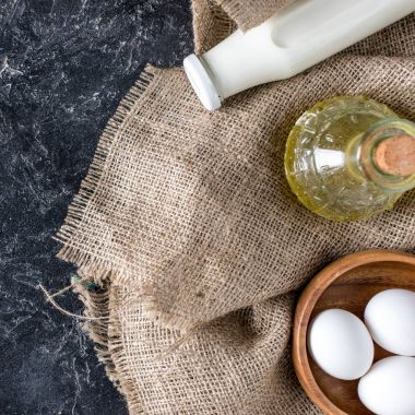 flat lay with bottles of oil and milk, raw eggs in bowl on sackcloth on dark surface