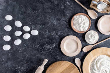 top view of raw eggs, flour, wooden plates, spoons and rolling pin for bakery on marble surface