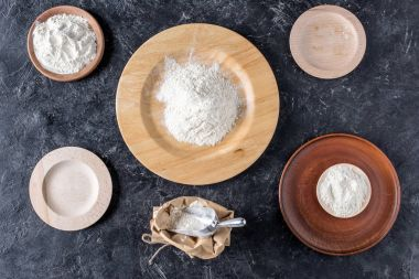 flat lay with arrangement of wooden plates and flour on dark marble tabletop