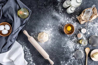 top view of raw dough, baking ingredients and cutlery on marble surface