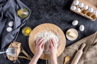 cropped shot of woman kneading dough for homemade bread