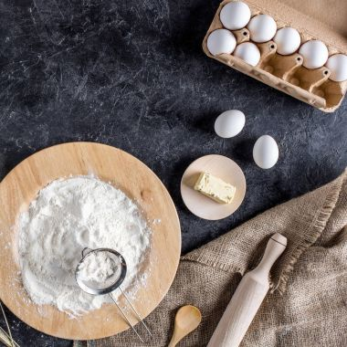 top view of raw eggs, flour, butter and kitchenware for bakery on dark tabletop