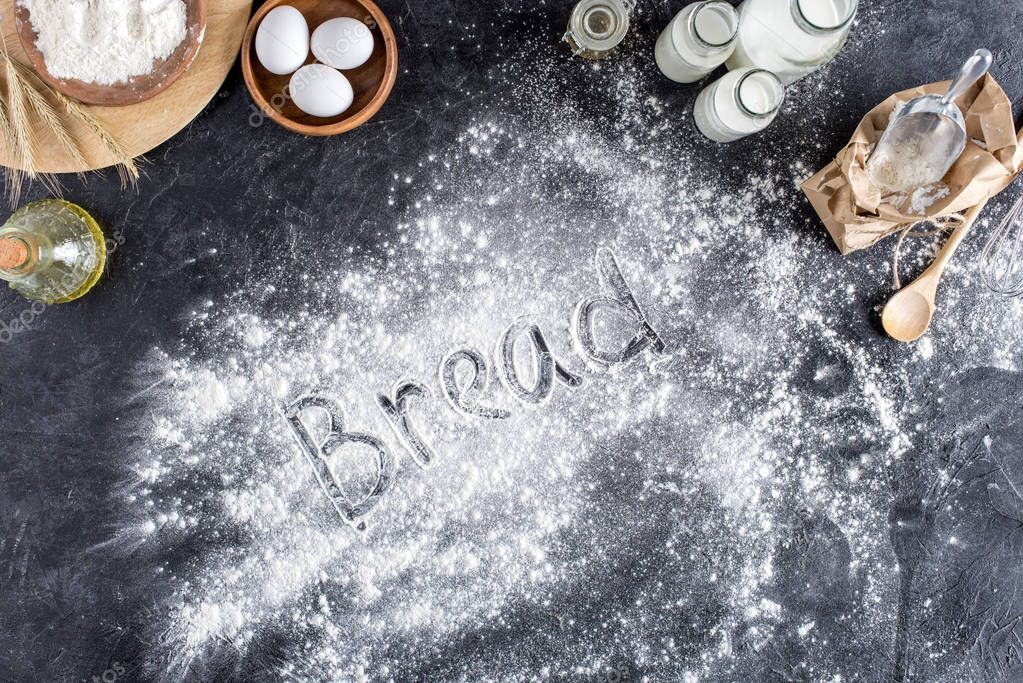 top view of bread lettering made of flour and various ingredients for baking on dark surface