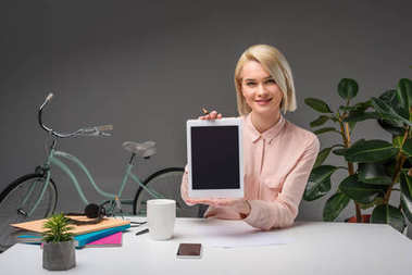 Portrait of smiling businesswoman showing tablet at workplace isolated on grey stock vector