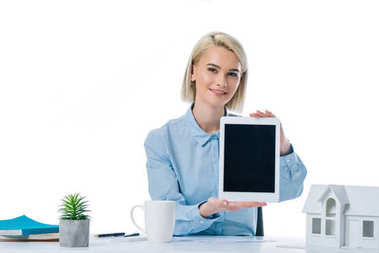 portrait of smiling real estate agent showing tablet at workplace isolated on white