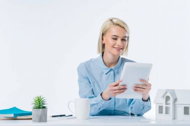 portrait of smiling real estate agent with tablet at workplace