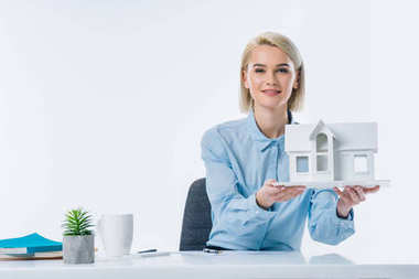 portrait of real estate agent showing house model at workplace
