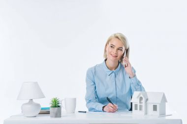 portrait of smiling real estate agent talking on smartphone at workplace with house model