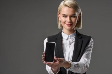 portrait of smiling woman showing smartphone with blank screen isolated on grey