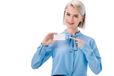 portrait of smiling woman pointing at empty card in hand isolated on white