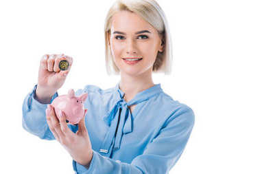 portrait of smiling businesswoman with piggy bank and coin in hands isolated on white