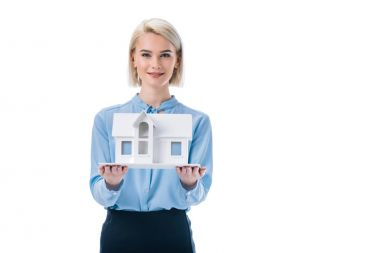 beautiful elegant agent presenting house model, isolated on white