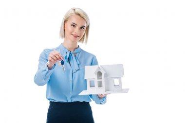 beautiful smiling realtor holding key and house model, isolated on white