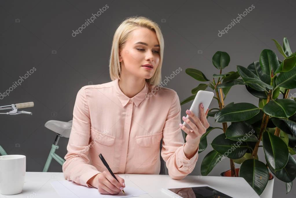portrait of young businesswoman using smartphone at workplace isolated on grey