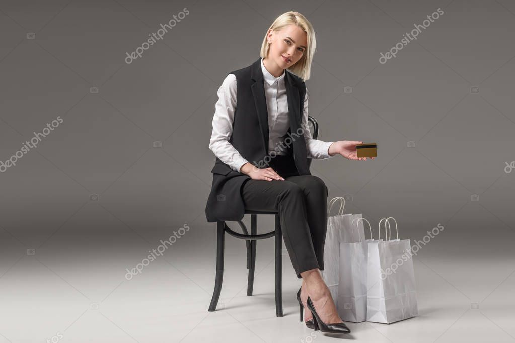 Stylish woman with credit card in hand sitting on chair near shopping bags