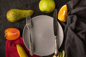 Fotografie top view of empty plate with cutlery and fresh fruits on tabletop