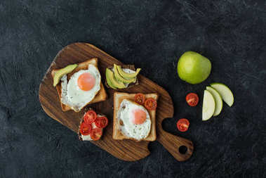 top view of toasts with fried eggs for breakfast on wooden cutting board on dark surface