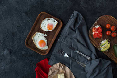 top view of fried eggs and tasty healthy snacks for breakfast on dark tabletop