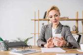 koncentrált üzletasszony használ smartphone, míg ült munkahelyi irodájában