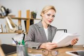 portrait of businesswoman doing paperwork at workplace in office