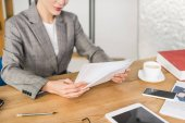 Fotografie cropped shot of businesswoman doing paperwork at workplace in office