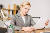 Fotografie concentrated businesswoman doing paperwork at workplace in office