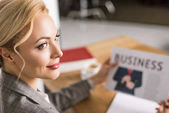 selective focus of businesswoman with newspaper at workplace