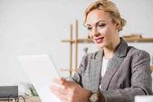s úsměvem podnikatelka s digitálním tabletu na pracovišti v úřadu