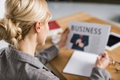 selective focus of businesswoman reading newspaper at workplace