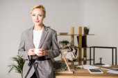 Photo portrait of smiling businesswoman with cup of coffee standing at table in office