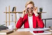 portrét podnikatelka v brýlích na pracovišti s dokumenty