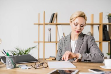 portrait of businesswoman checking time at workplace in office