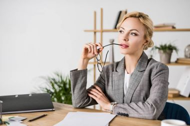 portrait of pensive businesswoman with eyeglasses looking away at workplace