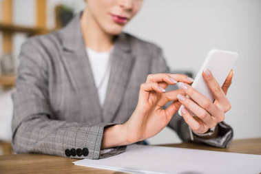 cropped shot of businesswoman using smartphone while sitting at workplace in office