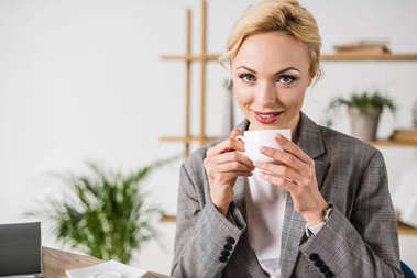Portrait of cheerful beautiful businesswoman with cup of coffee looking at camera stock vector