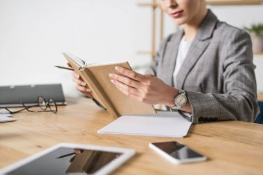 cropped shot of businesswoman with notebook sitting at workplace in office