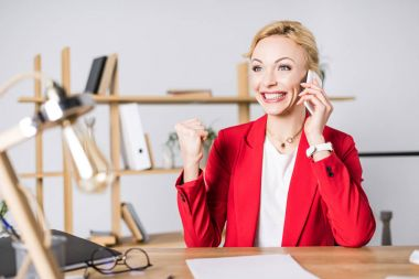 portrait of excited businesswoman talking on smartphone at workplace in office